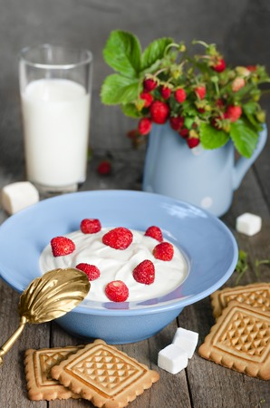 silver plated: Strawberry with cream in a bowl, cookies and milk in glass on old wooden surface. Bouquet with strawberries in a vase and antique spoon in a rustic style.