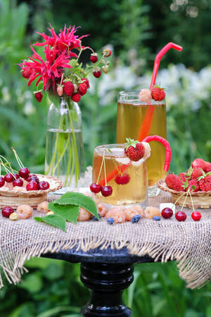 Iced tea and different berries on the table in the garden. Stock Photo