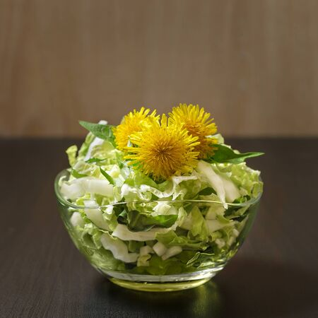 White cabbage salad in a glass vase decorated with dandelions. . Low key.