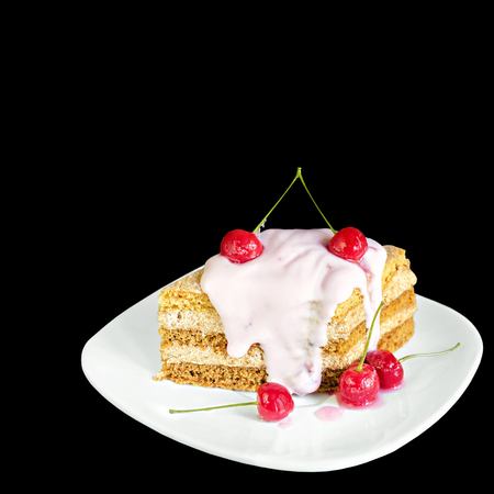 Piece of cake with cherries and yogurt on a plate, isolated on black background Stock Photo