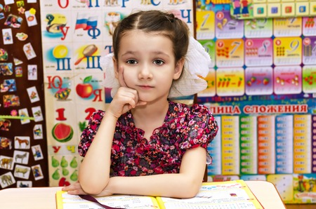 A little girl at her Desk, sad with the alphabet. Soon to go to school.