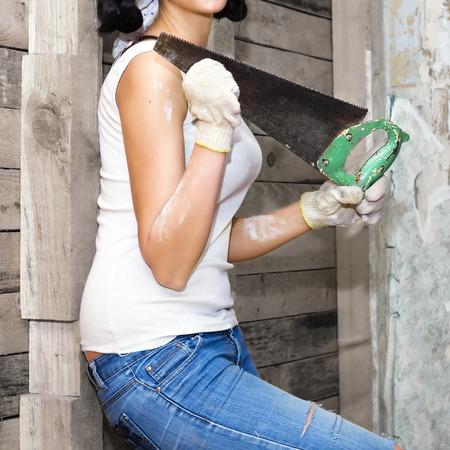 vestidos antiguos: La muchacha se coloca contra la pared de las viejas tablas. En ropa vieja y guantes de trabajo, mantener el viejo dicho. Torso sin cabeza Foto de archivo