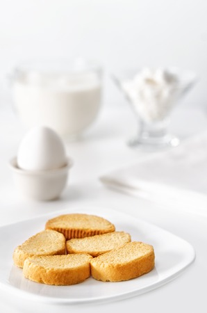 Breakfast white on white, high key and bokeh. A bowl of crackers, eggs, cheese and milk.