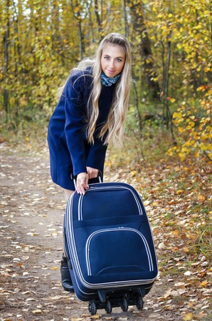 light blue lingerie: Girl with long blond hair, in a blue coat, yellow autumn background, bag on wheels Stock Photo