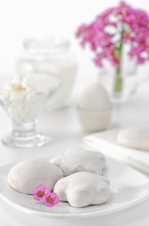 high key: Gingerbread, eggs, curd and milk for Breakfast. White background, high key, selective focus. Pink flowers