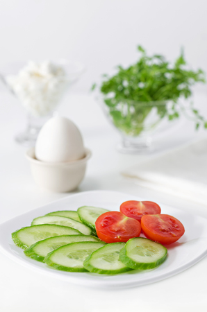 Sliced tomato and cucumber on a plate for Breakfast. The egg in the stand, herbs and cheese. High key on white background and selective focus.
