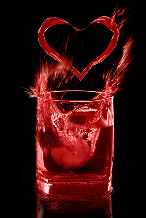 Red drink of love on black background, splash and heart