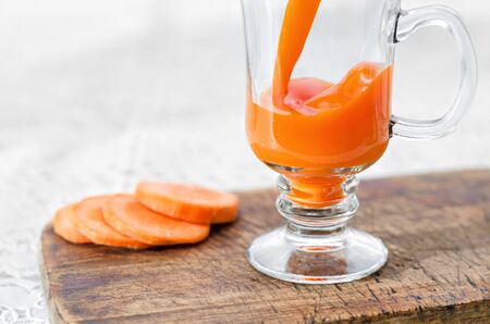 Carrot juice is poured into a glass Cup on a stem which stands on the table and the chopping Board, close cant see the edge. Selective focus and place for text.