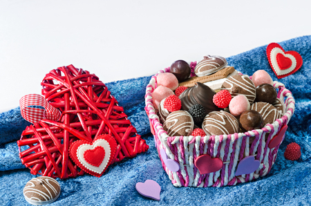 blue velvet: Candy basket, cookies and a decorative Valentines day hearts on blue velvet cloth and a white background. Selective focus.