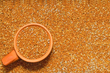 untreated: Background from untreated millet seed scattered on the surface and filled the Cup. Selective focus Stock Photo