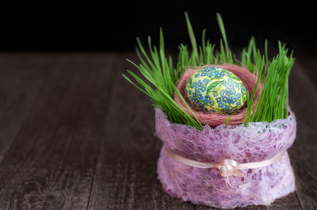 Decoupage Easter eggs and the germination of wheat in pot on wooden surface. Low key, selective focus.