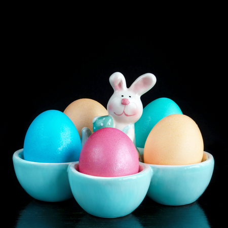 Easter colored eggs in the stand with a rabbit, on a black background. Cropping into a square.