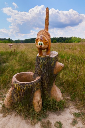 Berendeyevo, Russia, Moscow region, July 26, 2014, summer landscape with fabulous sculptures. Funny ginger cat on a tree stump. Selective focus.