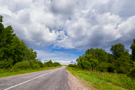 In the summer the road under Cumulus clouds, among the trees Stock Photo