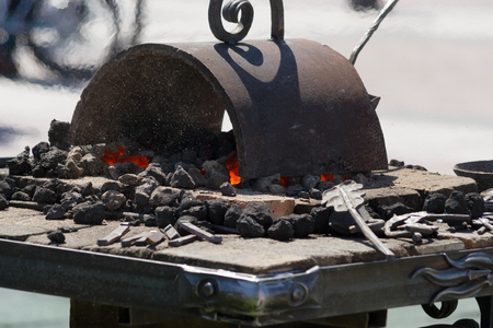 Forge with a burning coal in the open air
