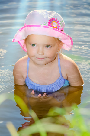 a bathing place: Portrait of a little girl sitting in the river water. Stock Photo