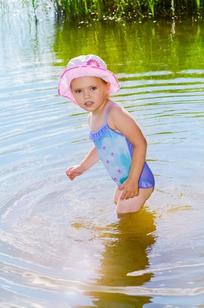 Beautiful little girl standing in River water.