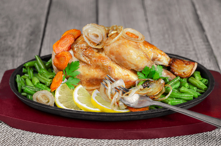 Fried chicken with vegetables in a cast iron skillet. Stock Photo