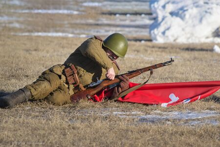 Festival of military history of Russia of XX century, Christmas maneuvers . Samara region, Togliatti, 5 January 2018. The standard bearer charges the rifle. Editorial