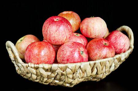 Ripe red apples in a wicker basket. Black background