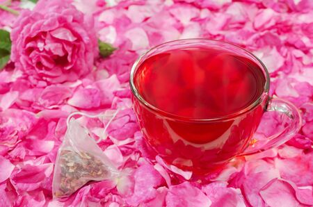 Glass Cup of hot flower tea, on a background of rose petals, lies next to a tea bag. Selective focus.