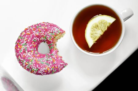 Tea with lemon and delicious beautiful donut with sprinkles.