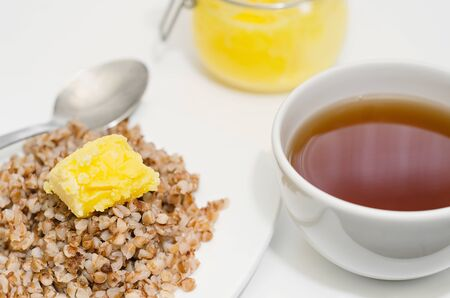 Delicious buckwheat porridge for Breakfast, with melted butter and tea. Selective focus