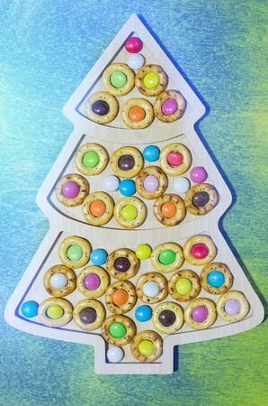 Plate in the form of Christmas tree with pretzels and sweets. Green wooden background and blue light effect