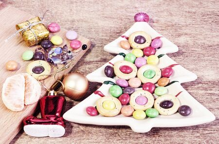 Plate in the form of Christmas tree with pretzels and sweets. Funny glass toy rat and Christmas decorations Banco de Imagens