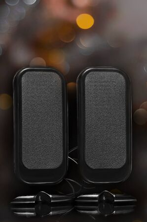Portable speakers vertical shape, on a black background with bokeh. Reklamní fotografie