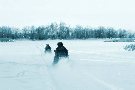 Men on two snowmobiles go on the winter river. The view from the back, toning and the effect of falling snow