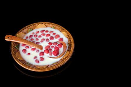 Dessert with wild strawberries and milk in a ceramic plate on a black background. A healthy vitamin diet made from natural products. Stock fotó