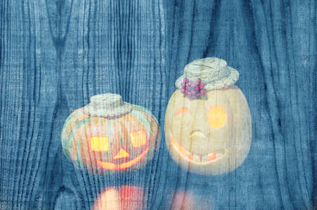 Blue wooden background with ghostly Halloween pumpkins. Plenty of space for text