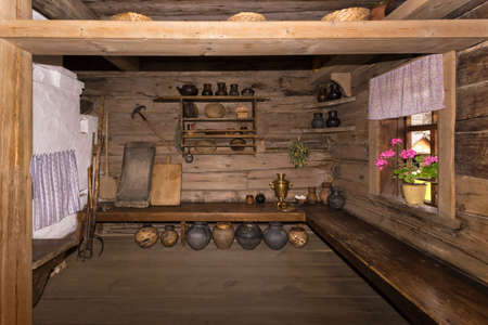 Vintage interior of a room with a Russian stove and old household items
