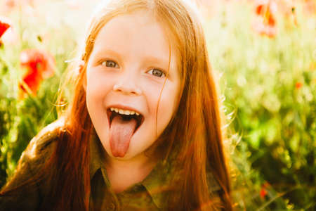 The little red-haired girl shows tongue. Foto de archivo