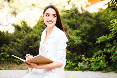 Retrato de una chica universitaria sonriente está sosteniendo el libro.