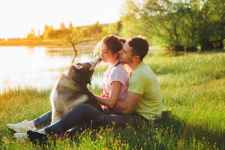 Lifestyle, happy family of two resting at a picnic in the park with a dog. Stock Photo