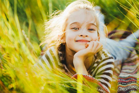 Portrait of a teenage girl in a striped T-shirt among the high green grass.
