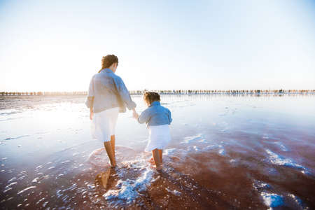 Stylish children in jeans jackets and white dresses on the tide line on the ocean. Stock Photo