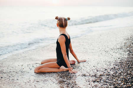 A teenage girl is sitting on the beach in a black swimsuit. Banque d'images