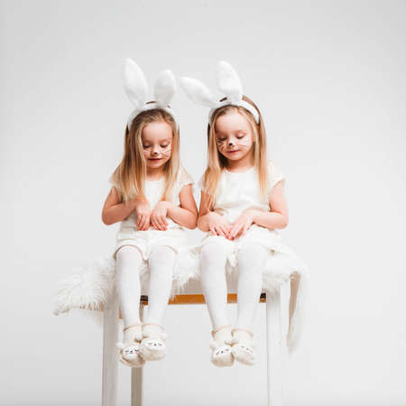 Little blonde twins in white dresses with rabbit ears. Studio photo on gray background. Kids celebrate Easter. 版權商用圖片