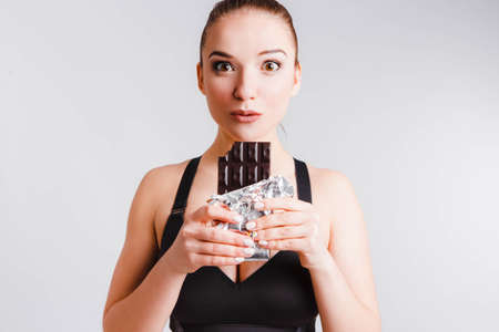 Beautiful fitness girl on a light gray background with chocolate. The concept of dealing with the desire to eat junk food.