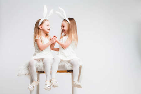 Little blonde twins in white dresses with rabbit ears. Studio photo on gray background. Kids celebrate Easter. Banque d'images