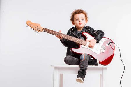 Foto de un niño pequeño rizos tocando música rock con guitarra eléctrica.