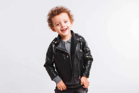 Little curly boy in black leather jacket on a light gray background. Rocker style 写真素材