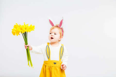 Smiling cute baby child in rabbit costumewith a bouquet of yellow daffodils on a white background. 写真素材