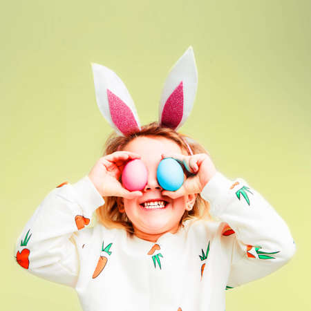 Studio shot of a happy little girl wearing bunny ears and holding up a colorful Easter egg in front of her eye. 写真素材