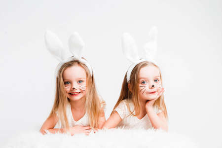 Little blonde twins in white dresses with rabbit ears. Studio photo on gray background. Kids celebrate Easter. 写真素材