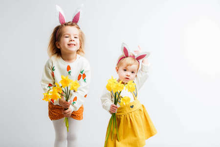 Happy easter. Funny children with rabbit ears celebrate Easter. Light gray background.
