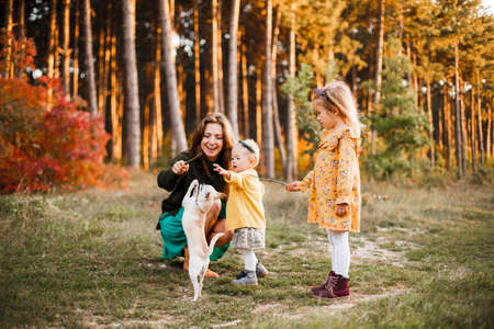Beautiful young mother and her little daughter walking in summer park. Woman and cute kid girl spending time together. Happy family , sunny day